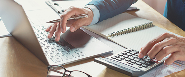 Small business owner calculating cost of benefits